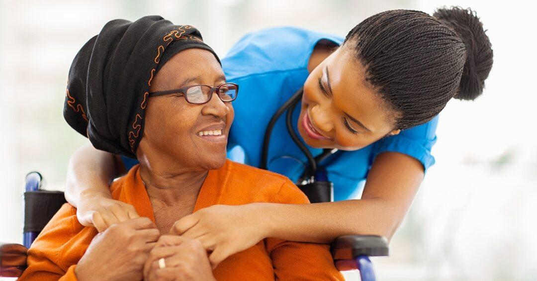 nurse embracing older woman in wheelchair