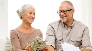 senior couple with money and papers