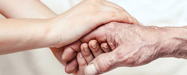 younger person clasping older person's hands