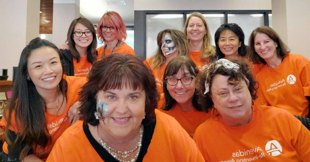 Avenidas Staff members in orange T-shirts and face paint at the 50th Birthday Bash