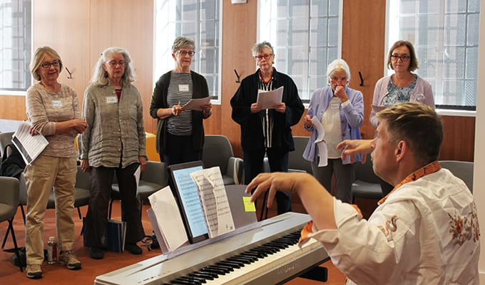 members of the Avenidas Choir sing while Michael Strelo-Smith plays the piano