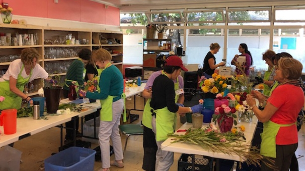 a group of Avenidas Blooms volunteers working on bouquets together