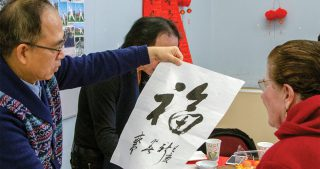 teacher demonstrating brush calligraphy at the Avenidas Chinese Community Center