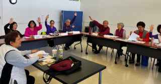 class members raise their hands in Teacher Ingrid's Intro to Cantonese class, 2019