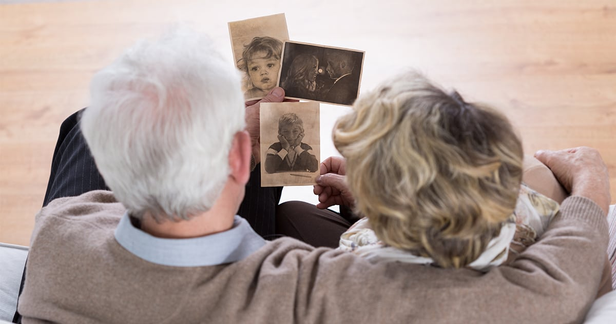 senior couple looks at sepia photographs