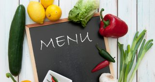"fresh vegetables surrounding a chalkboard with ""menu"" written on it"