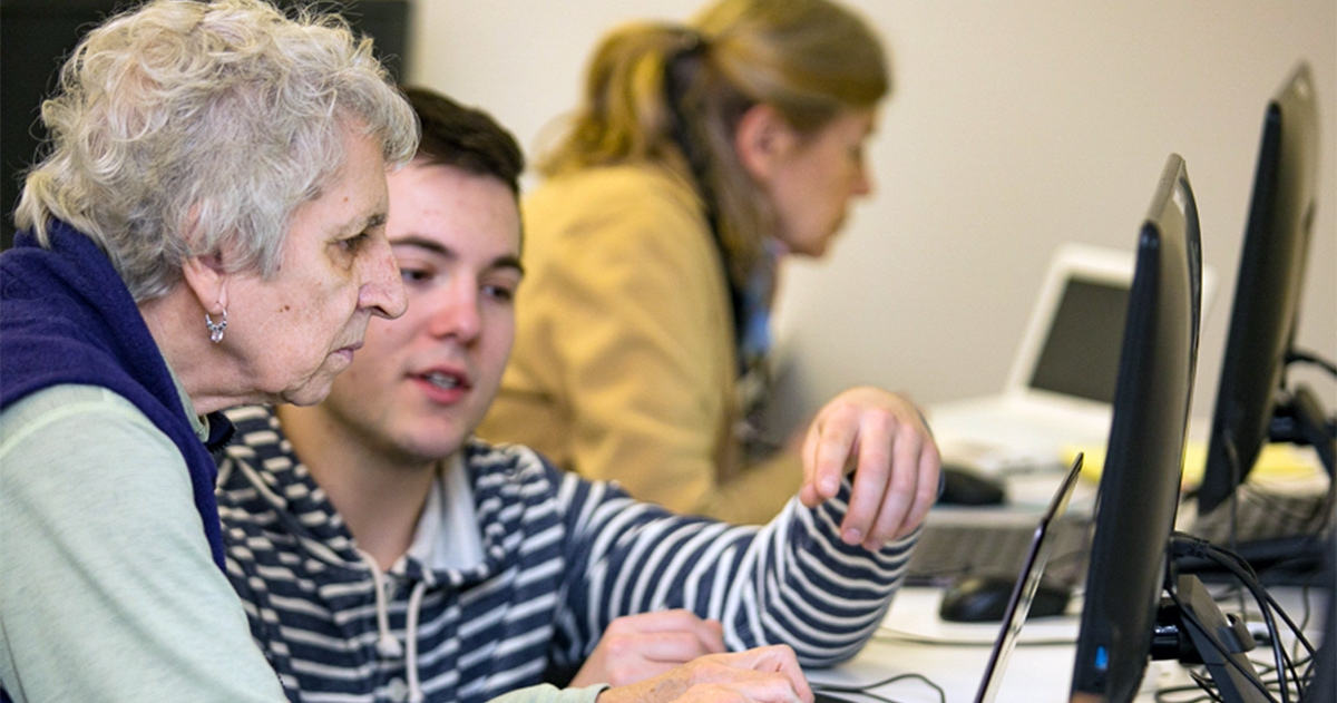 high-school student provides tech support to senior woman