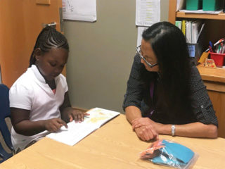 Young student learns to read with the help of an Avenidas Early Literacy Project volunteer.