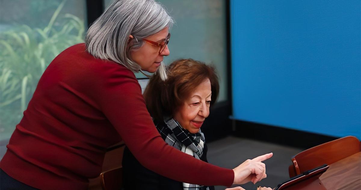 Senior Planet @Avenidas volunteer assisting Avenidas member with her tablet