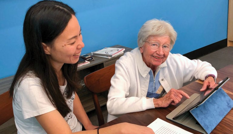 Palo Alto community member teaching an older woman to use a tablet at Senior Planet