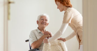 Female caregiver hands a sweater to a senior man in a wheelchair
