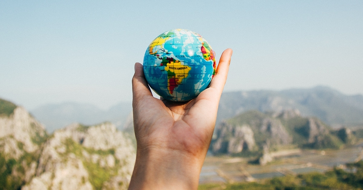 Hand holding up tiny globe in front of mountains