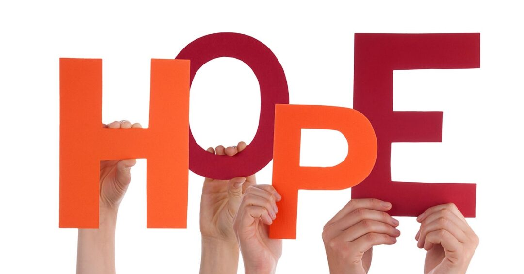 "hands holding orange and maroon letters spelling ""hope"""