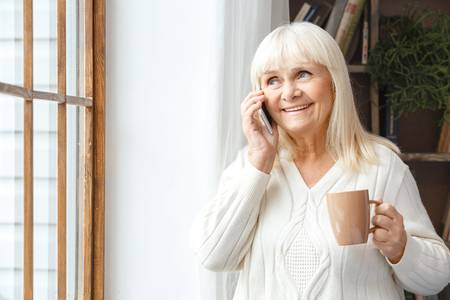 senior woman holding a cup of coffee and talking on her cell phone