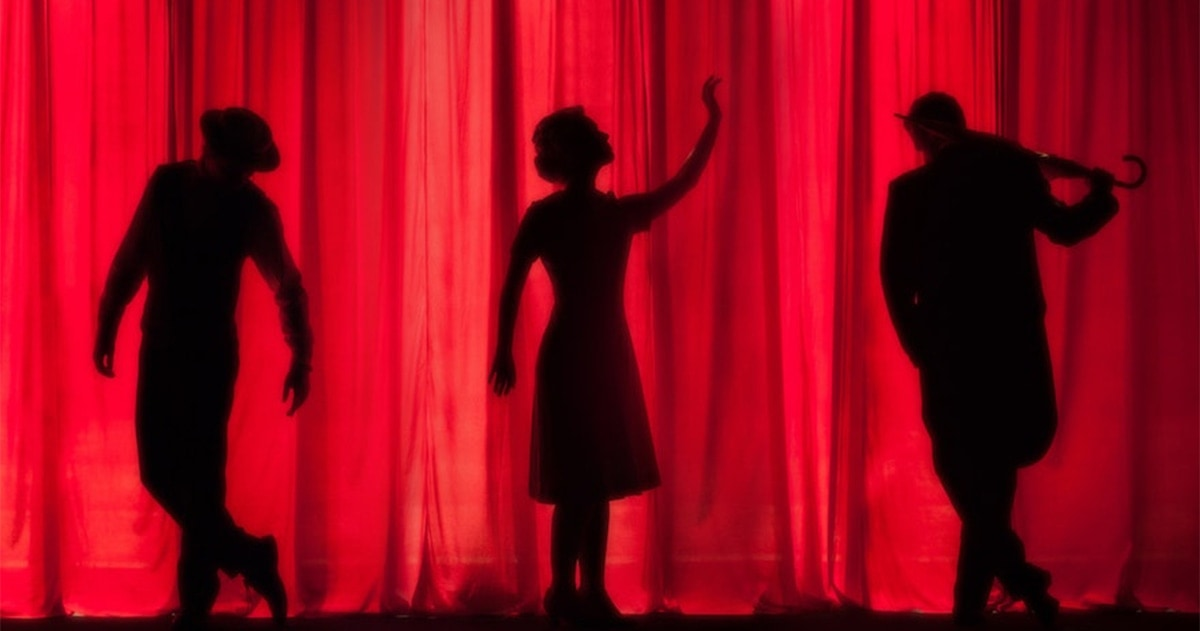 silhouettes of stage performers behind curtain