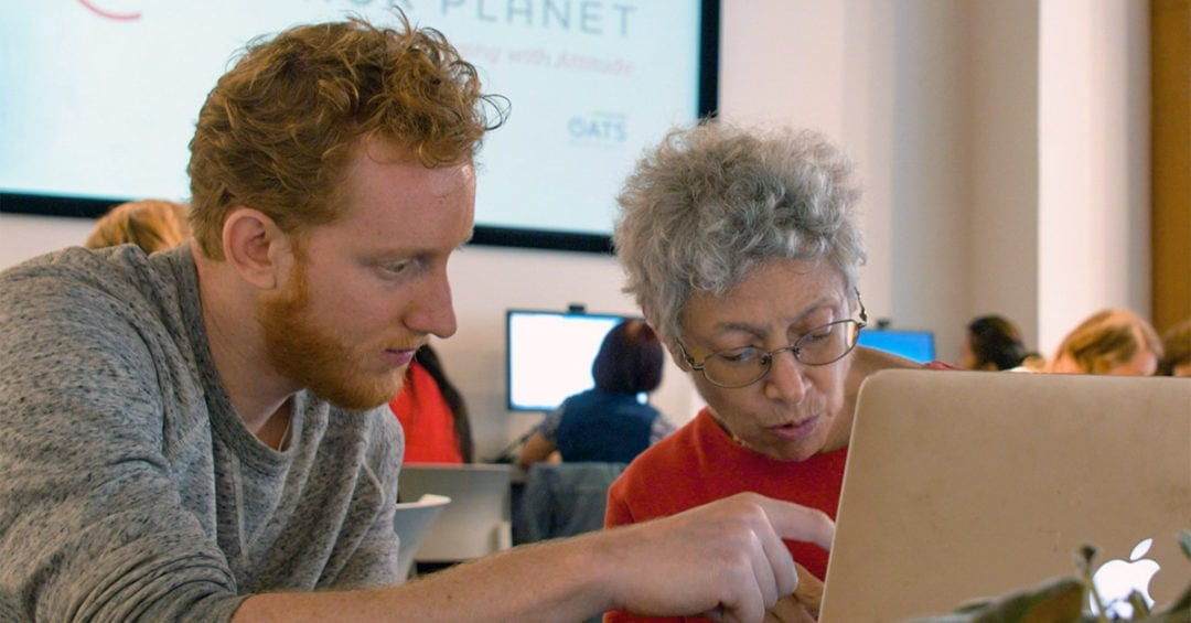 man with red hair and beard sitting with older woman at computer