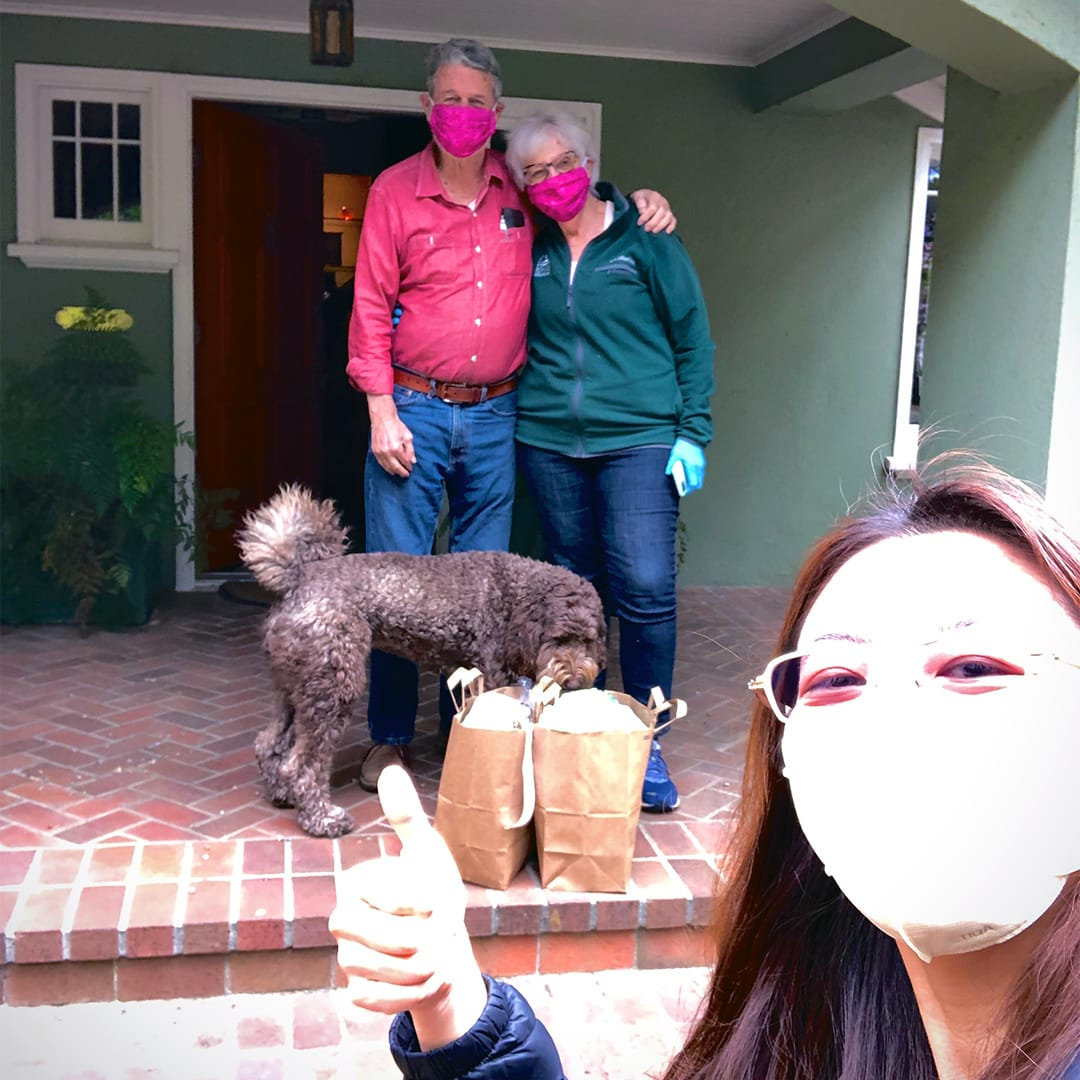 Sabrina Huang (front) at a safe distance from Eric and Gee Gee Williams and their dog, who is sniffing at the grocery bags. All three humans are wearing masks.