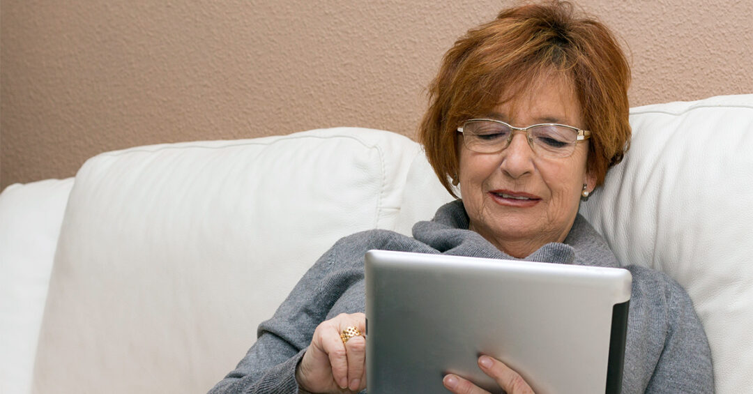 senior woman using an iPad while sitting on the sofa