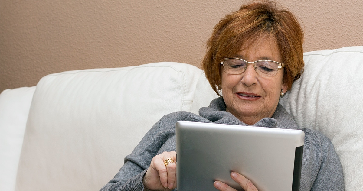 senior woman using an iPad while sitting on the sofa