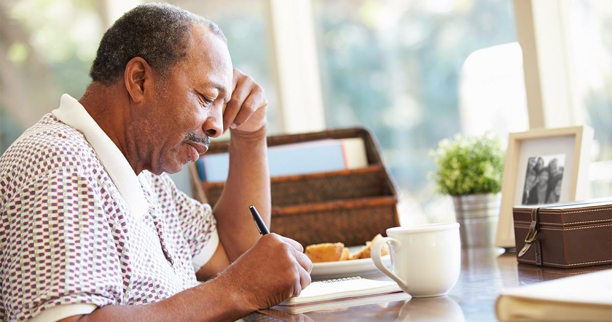 older black man writing his memoirs in a notebook