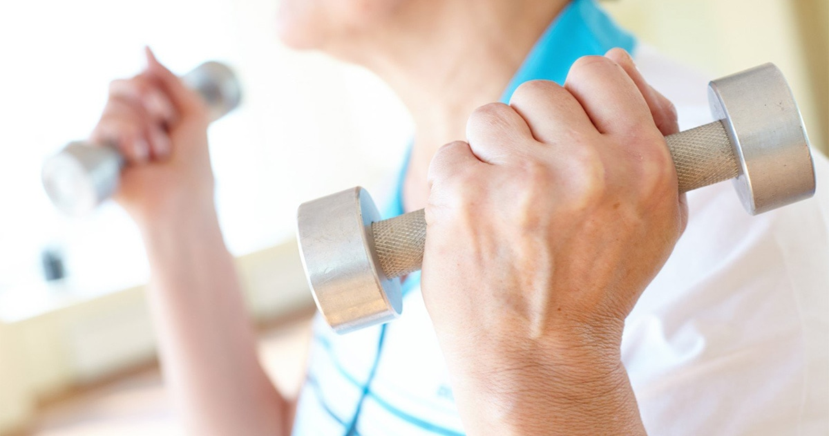 stock photo of older woman standing with hand weights
