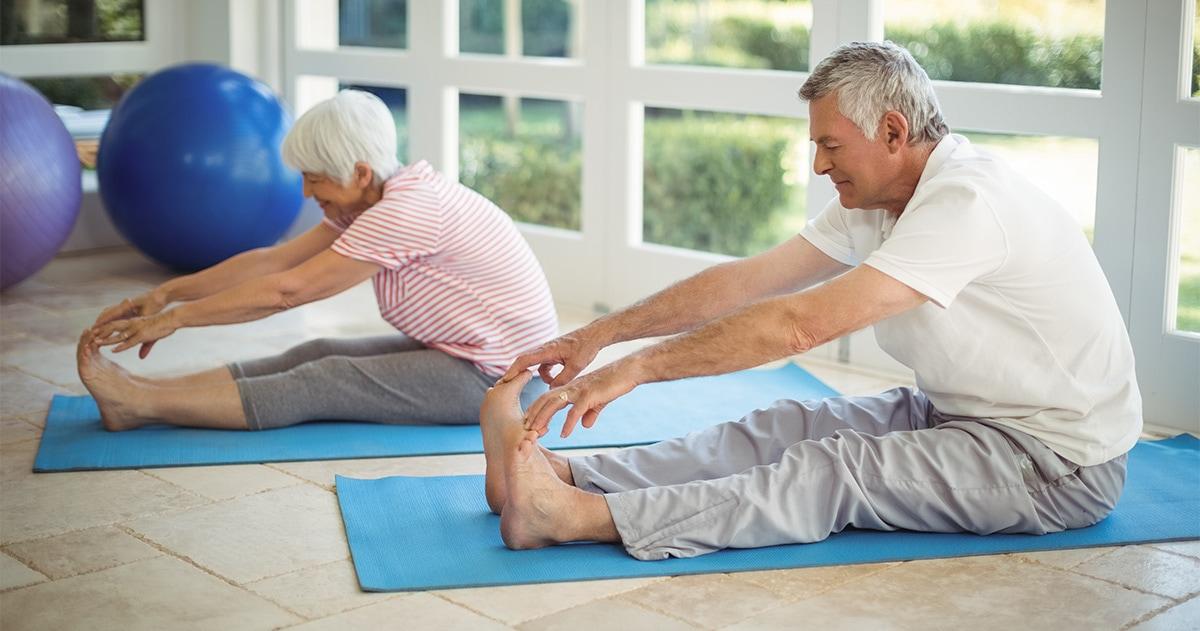 senior couple stretching on exercise mats