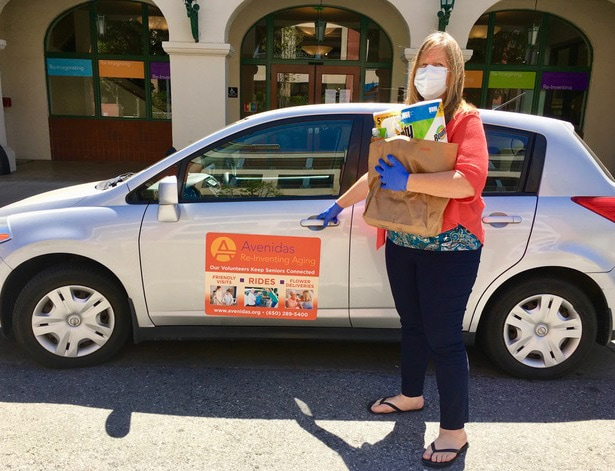 Avenidas Volunteer Services manager Jyllian Halliburton holding a full bag of groceries, wearing a face mask and nitrile gloves, standing in front of her car by the entrance to Avenidas @450 Bryant