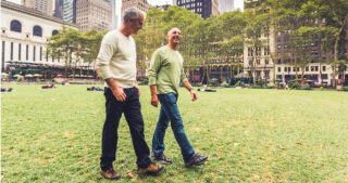 two gray-haired gay men walking in a city park