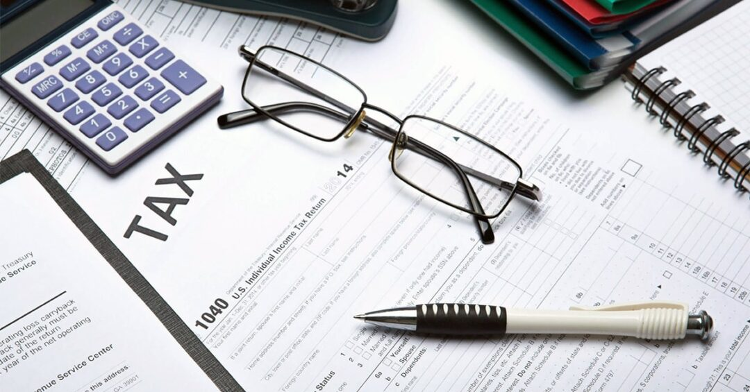 stock photo of tax forms, calculator, pen, reading glasses