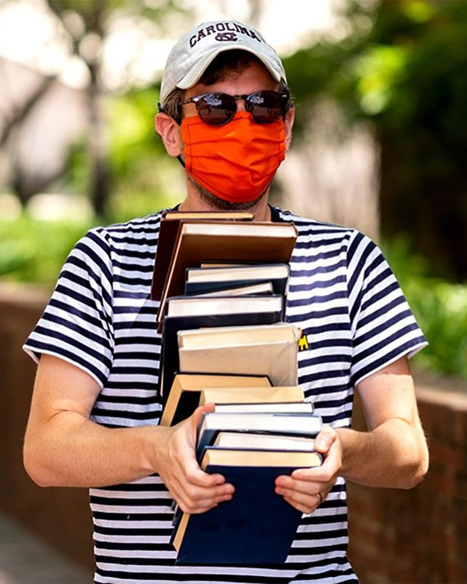 Man wearing white baseball cap, sunglasses, and a bright orange mask carrying a chin-high stack of library books