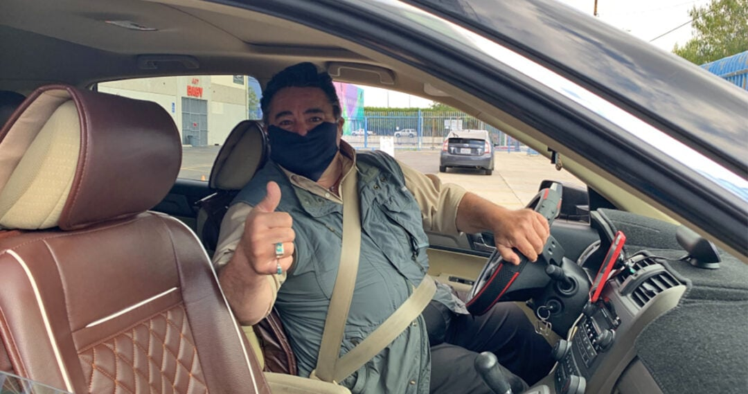 Lyft driver wearing a mask and giving a thumbs-up to the passenger.