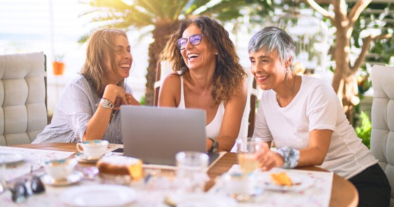 three mature women laughing together at a table with a laptop