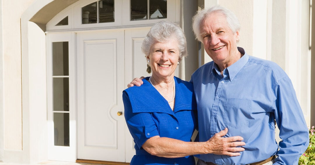 senior couple standing outside their home with their arms around each other
