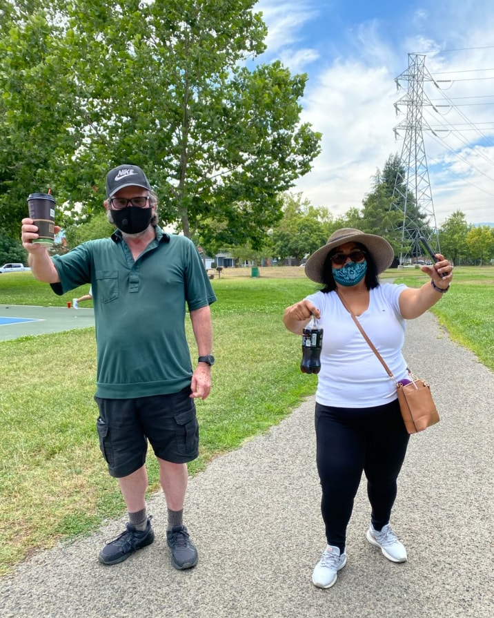 Grant (left) and Dina (right) pose in their masks on a flat gravel trail
