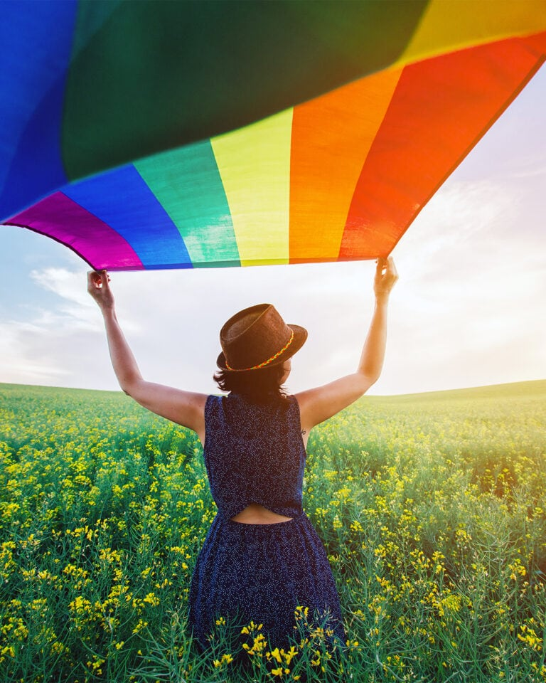 Woman standing in field of yellow flowers waving LGBTQ rainbow flag