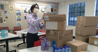 Dr. Albert Lam unpacking a box of disinfecting supplies for Operation PPE
