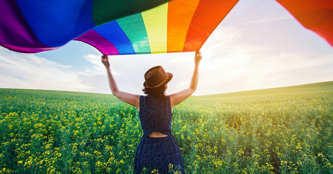 woman standing in field of yellow flowers waving huge rainbow flag