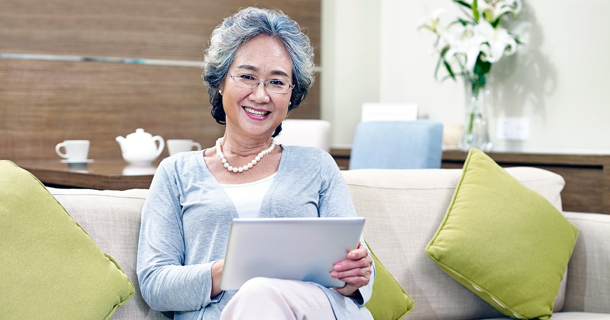 Older Chinese woman using a tablet on her sofa