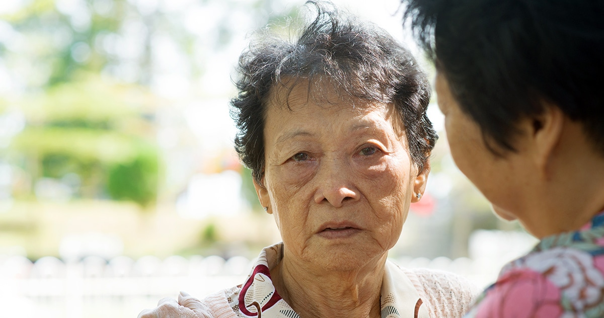 upset older Chinese woman faces the camera. Her adult daughter faces her, clasping her shoulder.