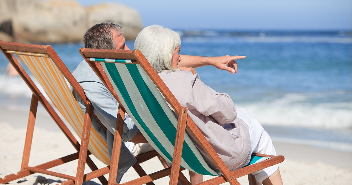 retired couple sitting in lawn chairs at the beach