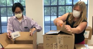 Albert Lam and Jyllian Halliburton open boxes of donated personal protection equipment