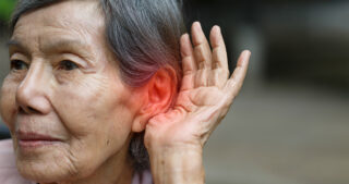 senior Asian woman holding her hand up to her ear. Red glow over ear to signify tinnitus.
