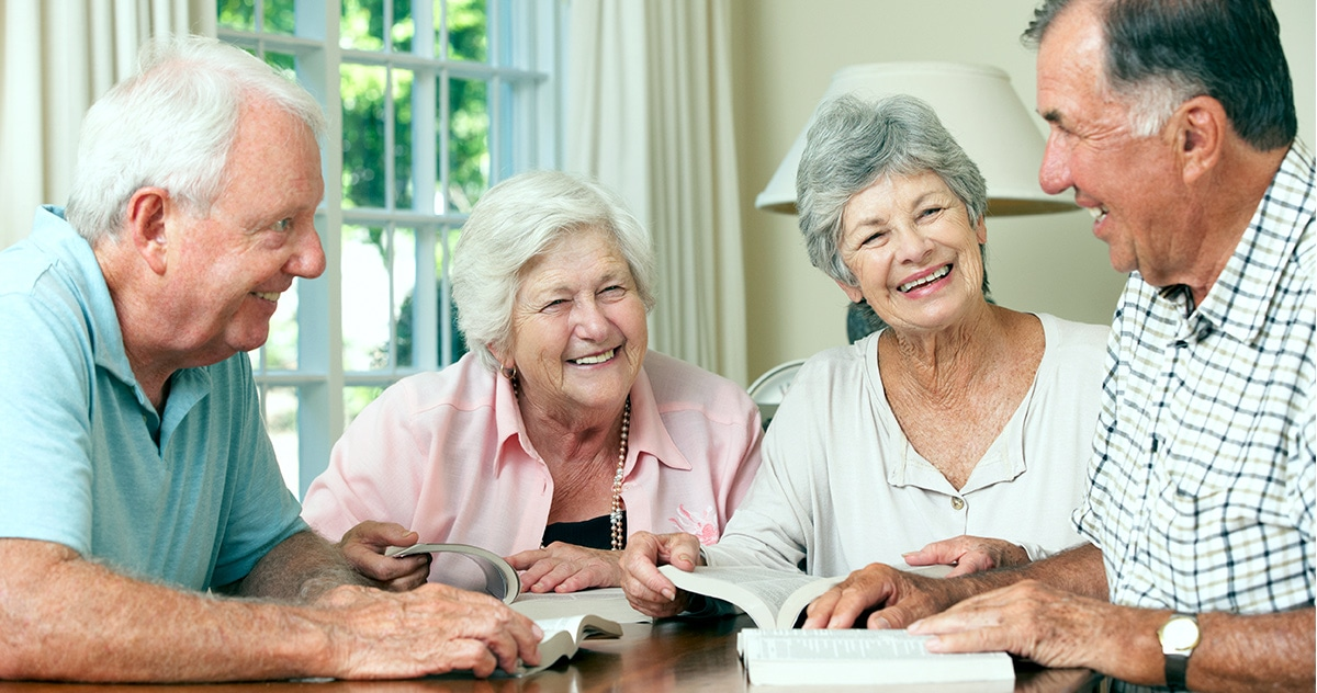 two senior husband-wife couples laughing together as they read from their book club books