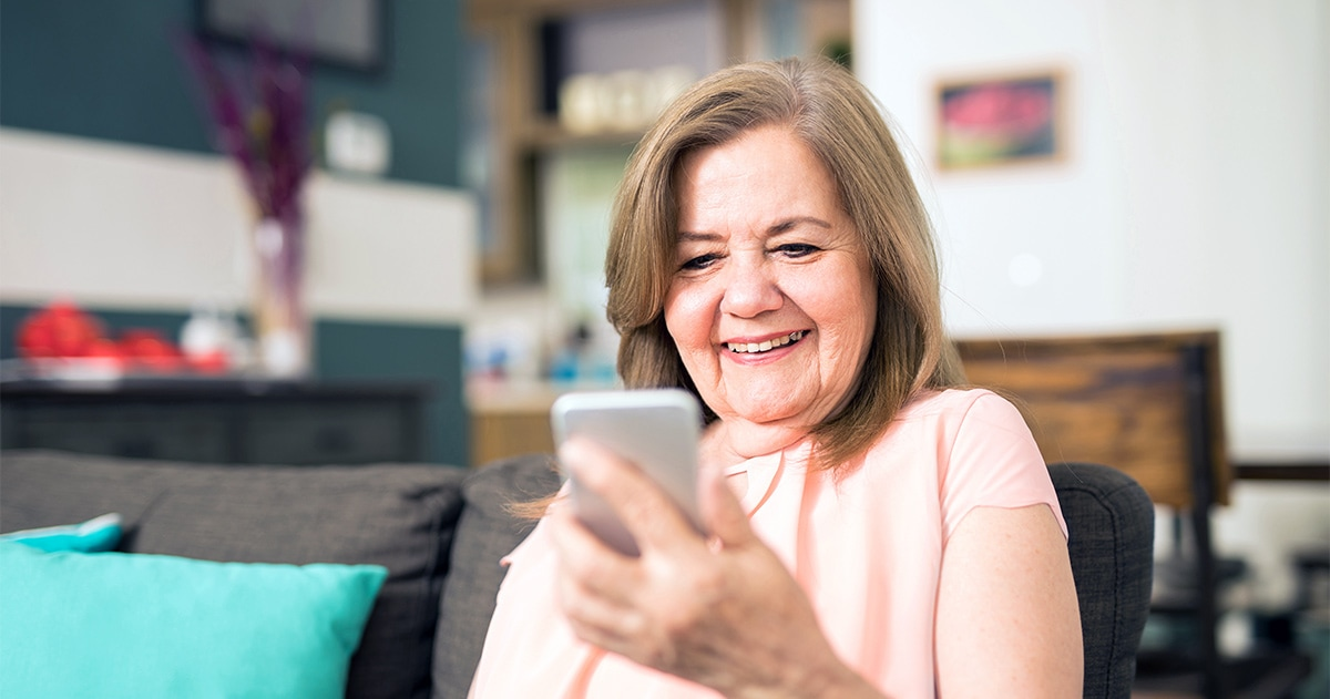 senior woman smiling as she reads a message on her smartphone