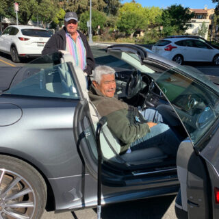 Avenidas Door to Door volunteer driver Stu Karlinsky stands by the driver's side of his light-blue convertible. Avenidas Rose Kleiner Center participant Daniel Alfaro is seated on the passenger side, with the door open and his cane standing ready for him to exit at his destination.